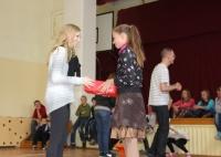 Laura Vīksniņa pasniedz jaunos apavus meitenei Kazdangas Māteru Jura pamatskolā