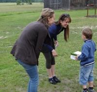 Kristīne Ģiga un Aina Budrēvica pasniedz jauno apavu pāri mazajam puikam Snēpelē